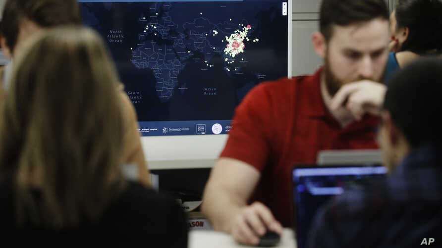 FILE - A worker at HealthMap, a system using artificial intelligence to monitor global disease outbreaks, mines health data to keep the system up to date in a work area at Boston Children's Hospital in Boston, Massachusetts, Feb. 13, 2020.