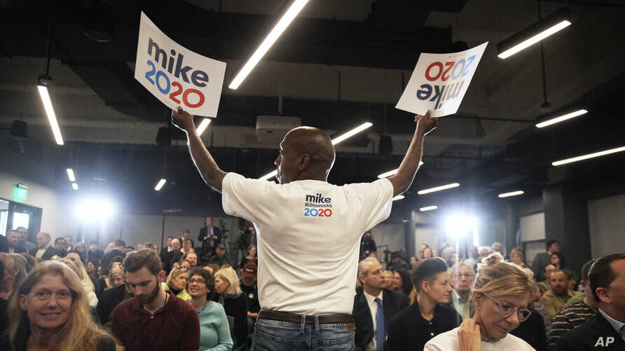 FILE - A campaign worker hands out signs at a campaign event for Democratic presidential candidate and former New York City Mayor Michael Bloomberg, in Providence, Rhode Island, Feb. 5, 2020.