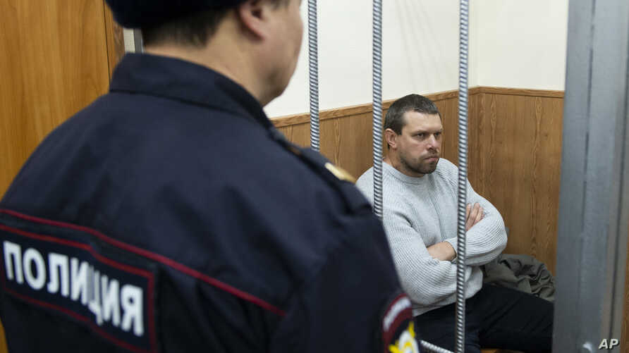 FILE - Former Russian police officer Denis Konovalov, right, sits in a cage prior to a court hearing in Moscow, Russia, Jan. 30, 2020.