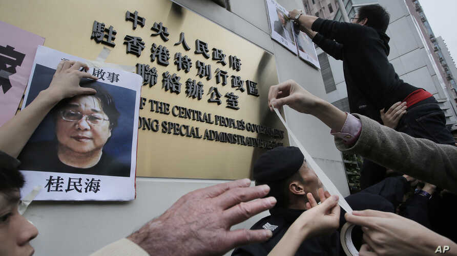 FILE - Activists paste photos of missing booksellers, one of which shows Gui Minhai at left, during a protest outside the Liaison Office of the Central People's Government in Hong Kong, Jan. 3, 2016.
