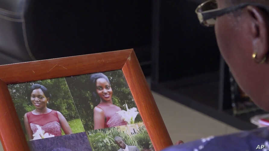 In this image taken from video, Margaret Ntale, whose three student daughters are stranded in Wuhan, China, looks at photographs of her children at her house in Kampala, Uganda, Feb. 27, 2020.
