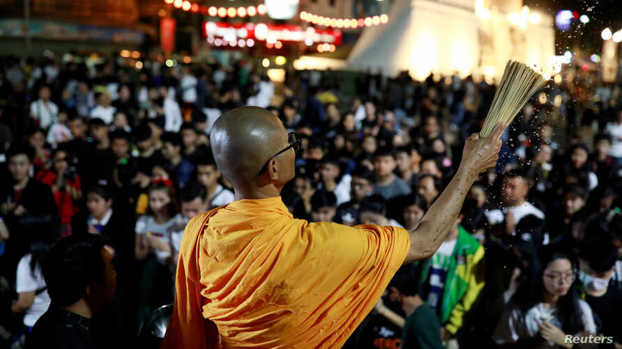 A buddhist monk sprinkles holy water as people pray for victims who died in a mass shooting involving a disgruntled Thai soldier on a shooting rampage, in Nakhon Ratchasima, Thailand, Feb. 9, 2020.