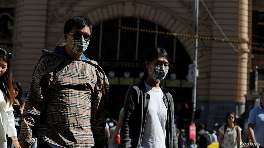 People wearing face masks walk by Flinders Street Station after cases of the coronavirus were confirmed in Melbourne, Victoria, Australia, Jan. 29, 2020.