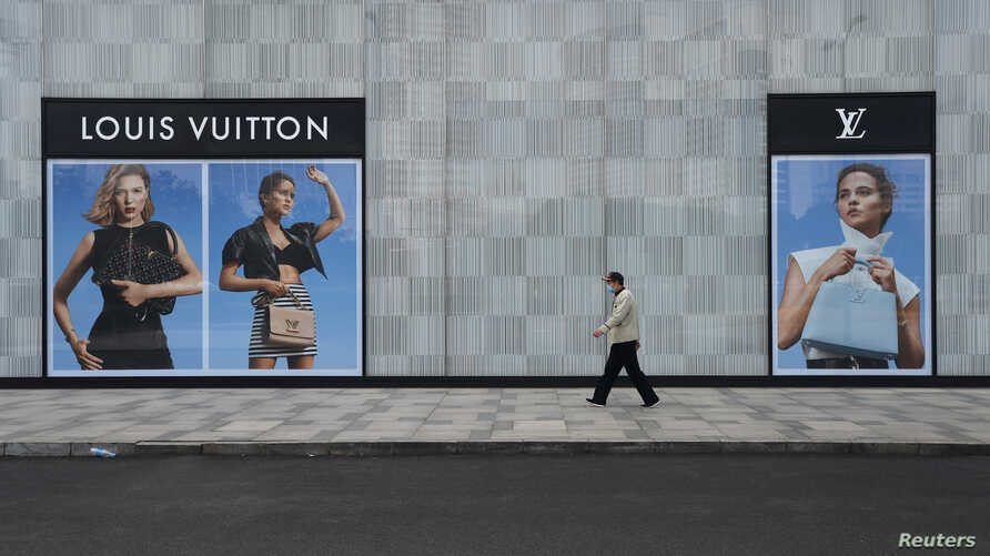 A man wearing a face mask walks past a store of French luxury brand Louis Vuitton at a shopping mall in Wuhan, the epicentre of the novel coronavirus outbreak, Hubei province, China, Feb. 25, 2020.