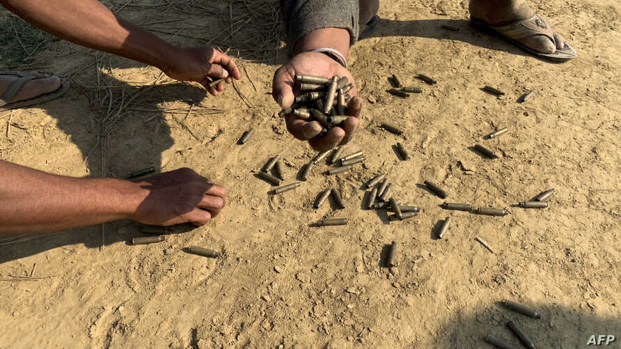 This photo taken on January 28, 2019 shows residents holding bullet shells in a village in Rathedaung township, Rakhine state,…