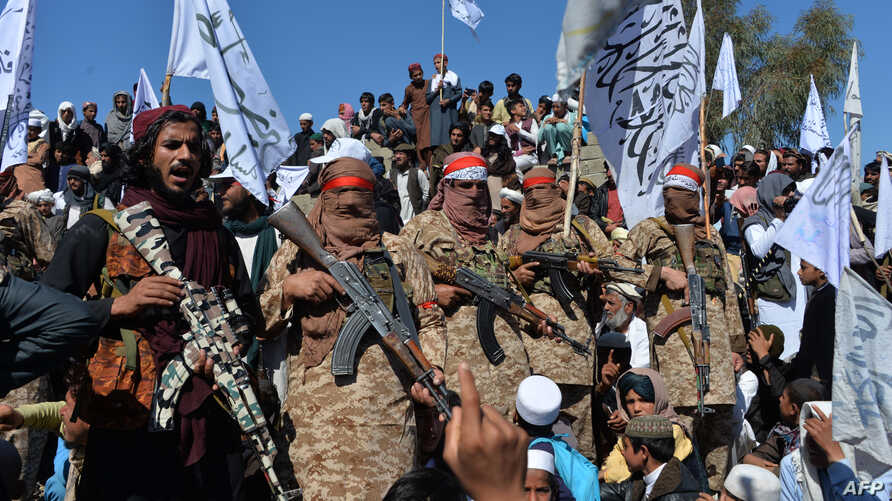 Afghan Taliban militants and villagers attend a gathering as they celebrate the peace deal and their victory in the Afghan…