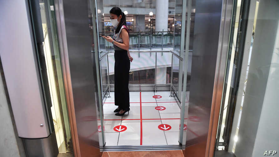 A woman stands in an elevator with markers on the floor for social distancing measures in a shopping mall amid concerns over…