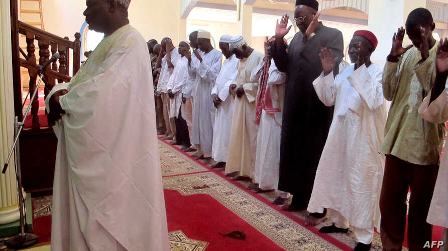 TO GO WITH AFP STORY BY REINNIER KAZE A photo taken on November 20, 2013 shows Imam Dalil Hayatou (L), leading the prayers at…