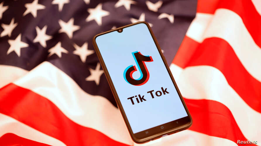 Tik Tok logo is displayed on a smartphone on the U.S. flag in this illustration