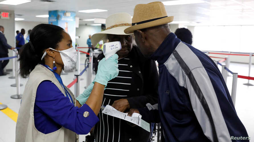 Travellers arriving into Haiti at the International Airport Toussaint Louverture get their temperature checked