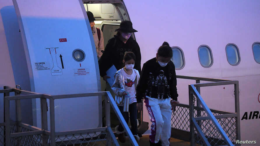 FILE - Australian evacuees who were quarantined on Christmas Island over concerns about the coronavirus disembark from a plane at Sydney Airport in Sydney, Australia, February 17, 2020.