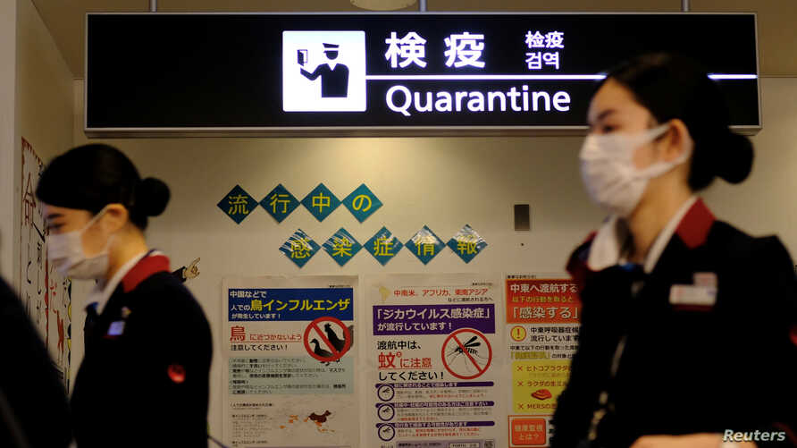Airline employees wearing protective face masks, following an outbreak of the coronavirus disease (COVID-19)