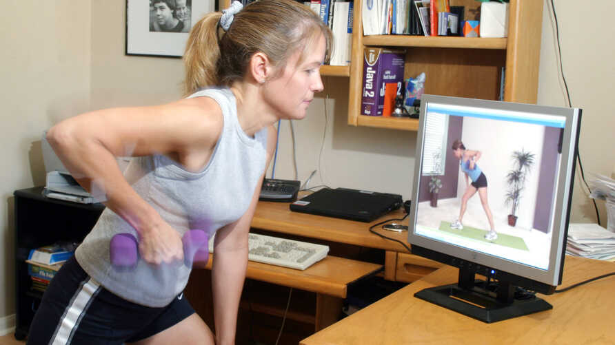 Michele Galindo exercises with a streaming video from a website while in her Austin, Texas, April 26, 2006.