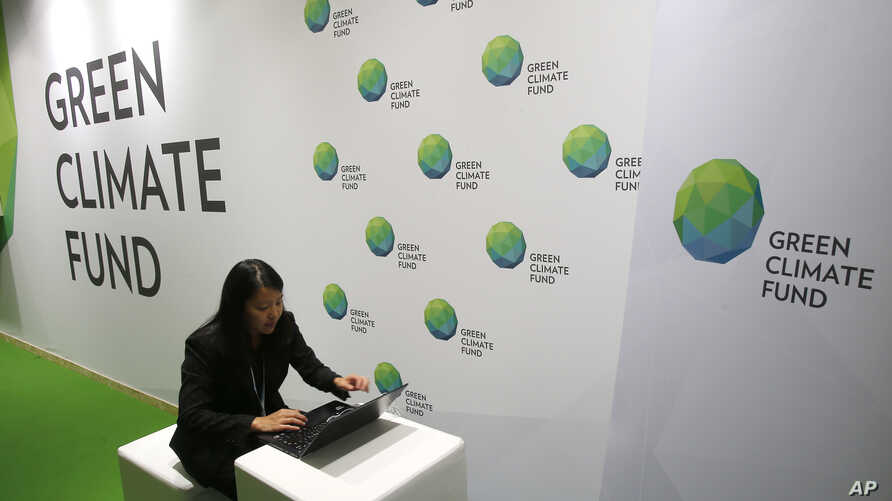 FILE - A woman works her computer at the Green Climate Fund stand at the COP21, United Nations Climate Change Conference, Monday, Nov. 30, 2015 in Le Bourget, north of Paris.