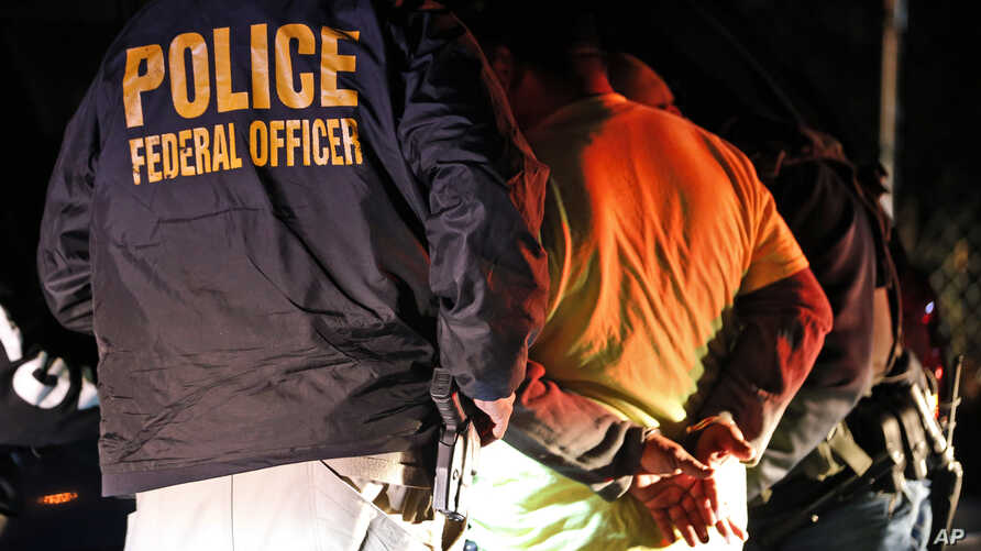 In this Oct. 22, 2018, photo U.S. Immigration and Customs Enforcement agents surround and detain a person during a raid