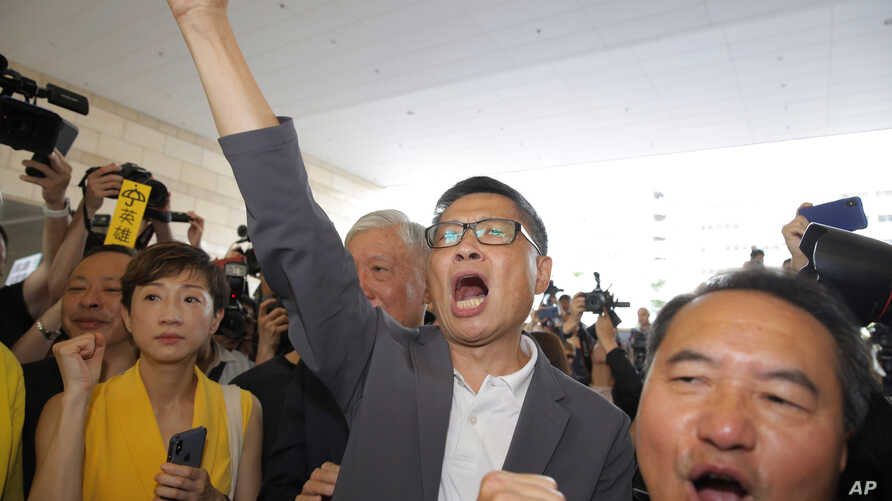 Occupy Central leaders, from left, Tanya Chan, Chan Kin-man and Lee Wing-tat chant before entering a court in Hong Kong,…