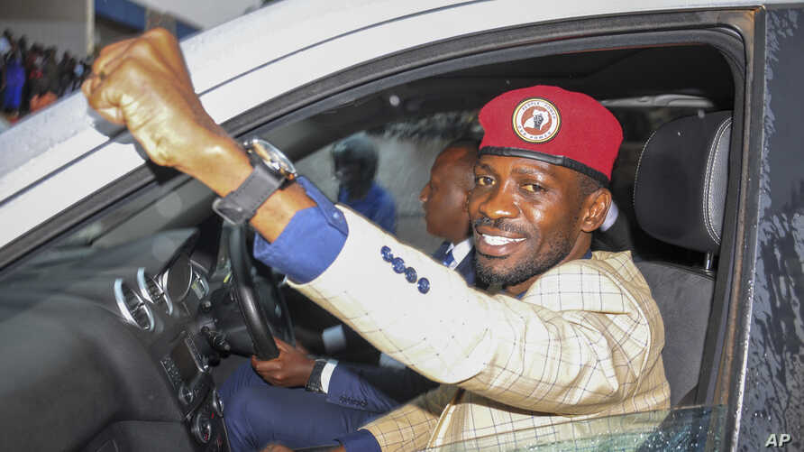 FILE - Ugandan presidential hopeful and political activist Bobi Wine, whose real name is Kyagulanyi Ssentamu, raises his fist in the air to gathered supporters as he leaves after meeting with the Electoral Commission, in Kampala, Uganda, Jan. 9, 2020.