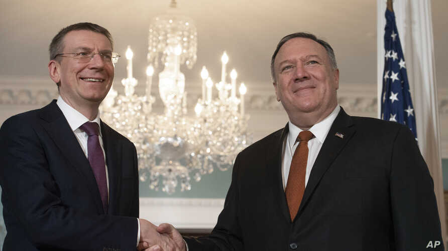 Secretary of State Mike Pompeo, right, shakes hands with Latvian Foreign Minister Edgars Rinkevics, during a media opportunity…
