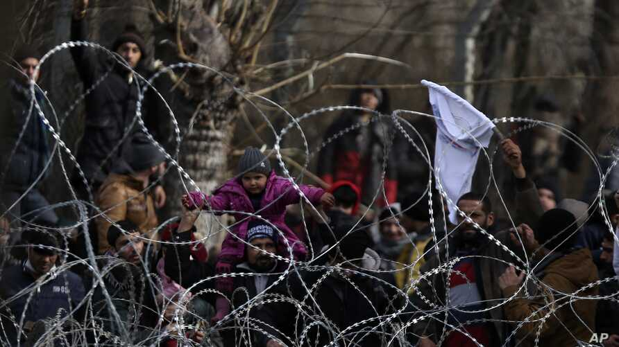 Migrants stand behind a fence near the Kastanies border gate at the Greek-Turkish border, March 2, 2020.