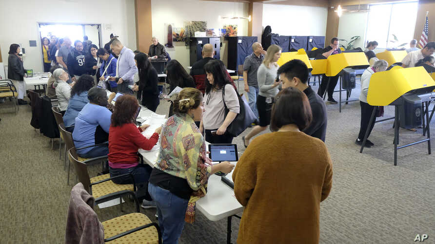 Voters cast their ballot on the Super Tuesday, at a voting center in Alhambra, Calif., Tuesday, March 3, 2020. (AP Photo/Ringo…