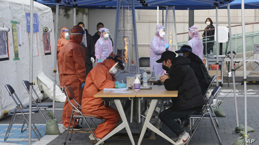 Medical staff wearing protective suits talk with people with suspected symptoms of new the coronavirus, at a testing facility.