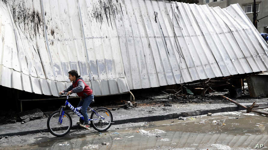 A child rides his cycle as inspects the damaged and burned shops at the main market in Nusseirat refugee camp, central Gaza Strip, March 6, 2020.