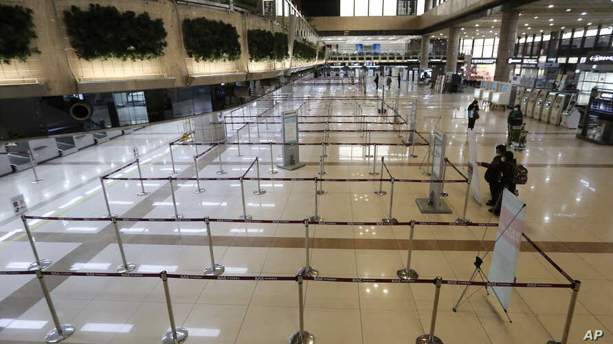 Check-in counters of Japanese airlines are deserted at Gimpo Airport in Seoul, South Korea, Saturday, March 7, 2020.