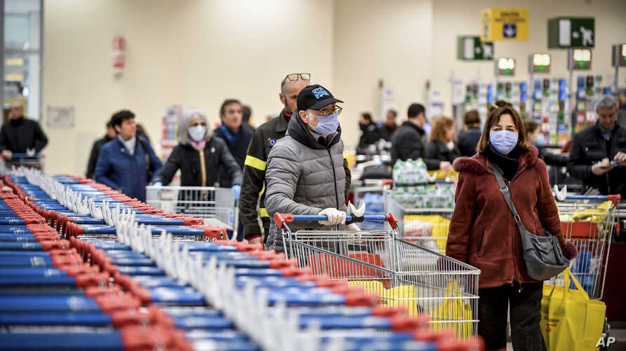 People wear masks at a supermarket in Milan, Italy, March 8, 2020.