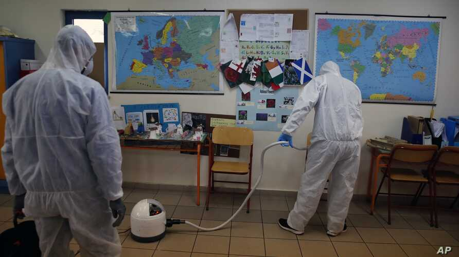 Workers wearing protective suits spray disinfectant inside a classroom at a primary school in Athens, March 9, 2020.