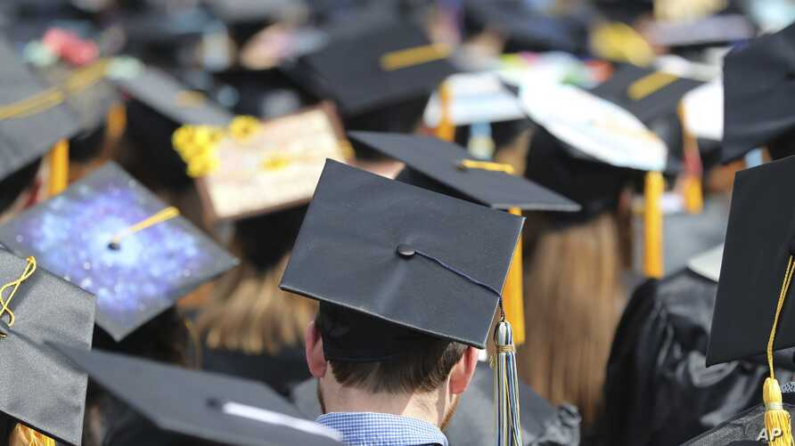 FILE - In this May 5, 2018, file photo, graduates at the University of Toledo commencement ceremony in Toledo, Ohio. Colleges…