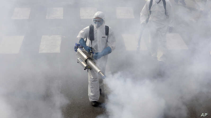 Firefighters disinfect a street against the new coronavirus, in western Tehran