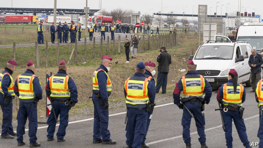 Police officers block the road at the Austrian border in Hegyeshalom, northwestern Hungary, Tuesday, March 17, 2020. By noon an almost 20-kilometer long line of cars waited on the Austrian side of the border.