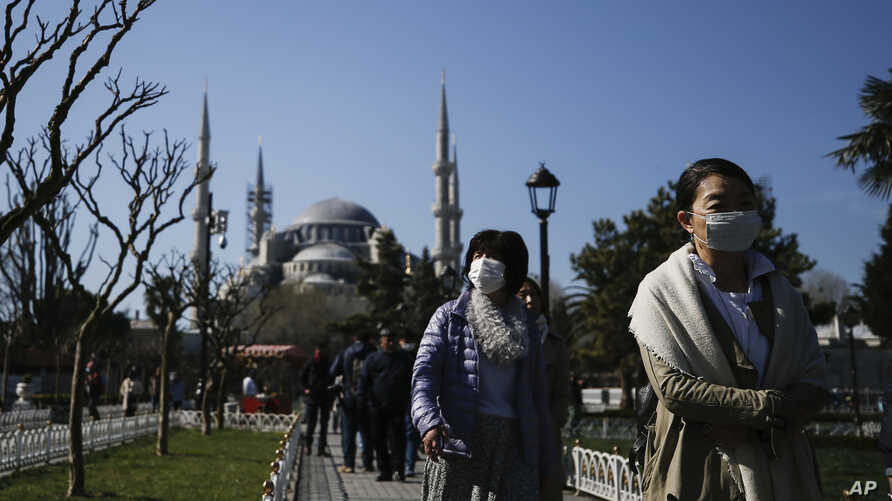 Tourists walk as municipality workers wearing a face mask and protective suits disinfect the area surrounding the historical Sultan Ahmed Mosque, also known as Blue Mosque, amid the coronavirus outbreak, Istanbul, March 21, 2020.