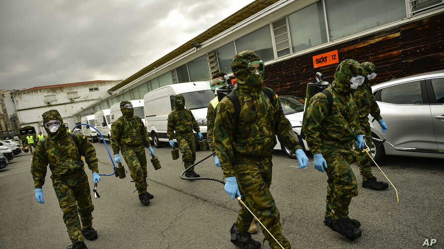 Member of Military Emergency Unit walk with special equipment to disinfect areas to prevent the spread of the coronavirus,…