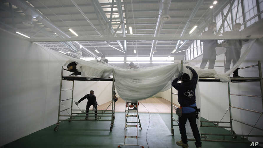 Workers, volunteers and Italian Army Alpini corps prepare the intensive care room of a new hospital being built in the spaces of the Bergamo Fair, in Bergamo, Italy, March 26, 2020.