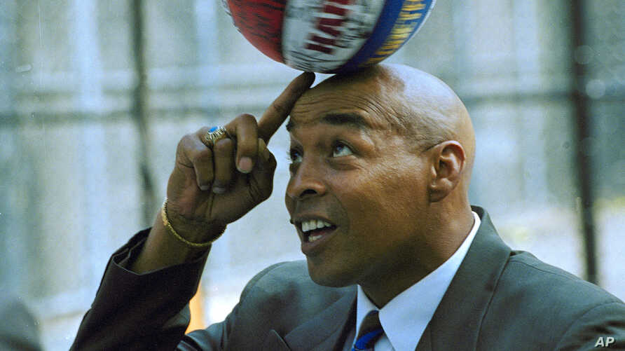 Former Harlem Globetrotters' star Curley Neal does some of his old fancy ball-handling as he transfers a spinning ball from his…