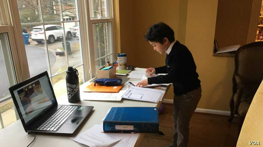 Eunjung's 2nd-grader son sorting out his worksheets from school. (Eunjung Cho/VOA)