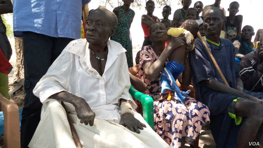 Monica Yom Kulang (with broken arm) sitting under a desert date tree with her family members in Malek village, Jonglei state