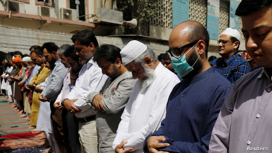 A man wears a protective mask as a preventive measure amid coronavirus fears, as he attends Friday prayers with others in…