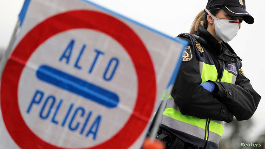 A border police officer wears a protective face mask at the last toll gate entering Spain from France, following an order from…