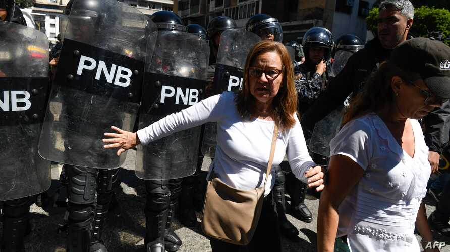 FILE - Supporters of the Venezuelan opposition confront members of the Bolivarian National Police as they attempted to block a main avenue during a protest against the government of President Nicolas Maduro, in Caracas, Venezuela, Nov. 18, 2019.