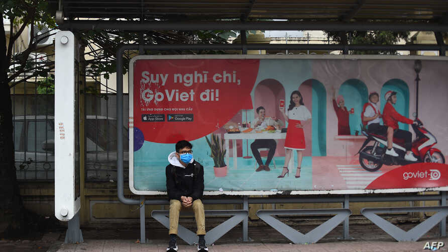 FILE - A man wearing a protective mask sits at a bus stop in Hanoi, Vietnam, Feb. 4, 2020.