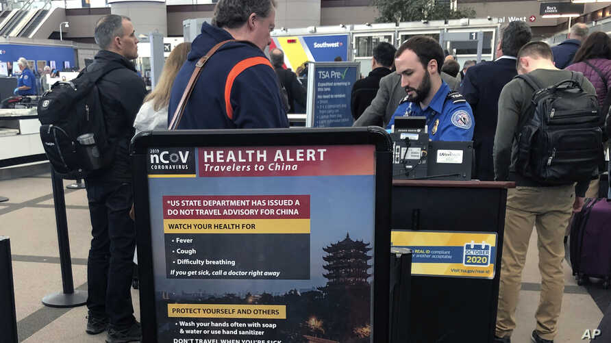A health alert for people traveling to China is shown at a TSA security checkpoint at the Denver International Airport in Denver, Colorado, March 2, 2020.