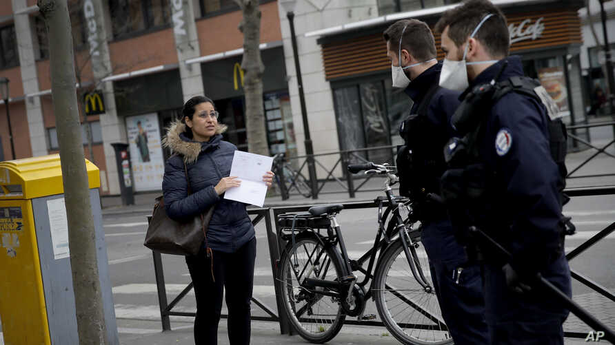 Police officers check a pedestrian in Boulogne Billancourt, March 18, 2020.