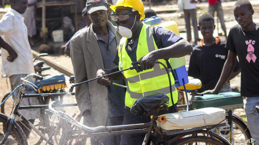 A man sprays disinfectant on a bicycle taxi in the Kibuye Market area of Kisumu, western Kenya, March 25, 2020. Riot police in the city has fired tear gas into a market Wednesday disperse crowds in hopes of limiting the spread of the coronavirus.