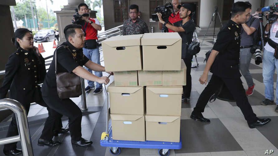 FILE - Anti-corruption agency's staff transport documents for 1MDB case to Kuala Lumpur high court, in Kuala Lumpur, Malaysia, Aug. 28, 2019. The investigation into one of the world's biggest corruption scandals has been thrown into uncertainty.