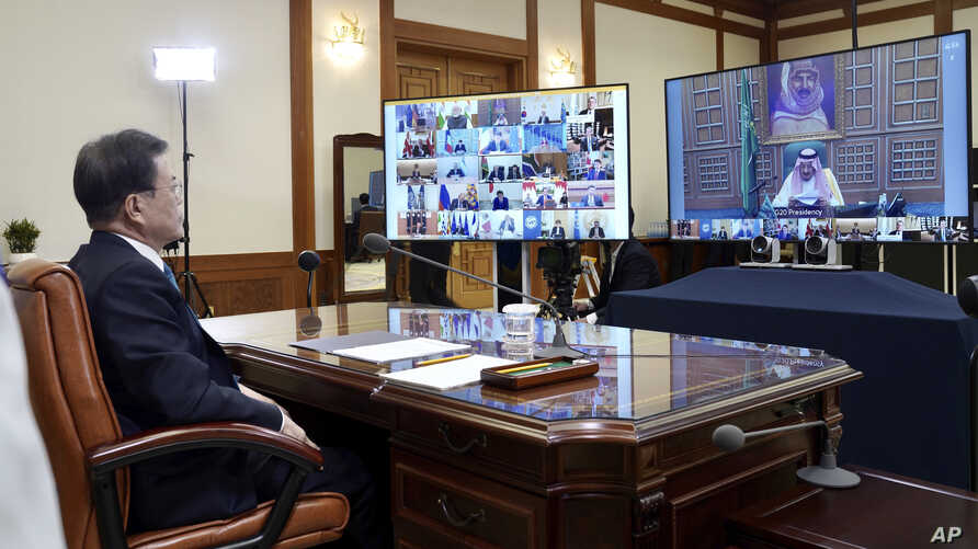 In this photo provided by South Korea Presidential Blue House via Yonhap News Agency, President Moon Jae-in attends G-20 virtual summit to discuss the coronavirus outbreak at the presidential Blue House in Seoul, March 26, 2020.