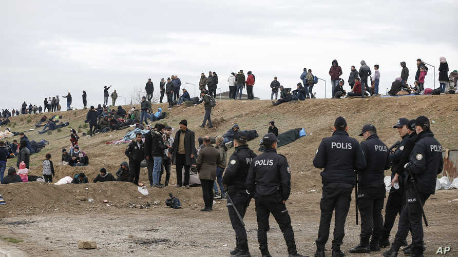 Turkish police stand by migrants camping in Edirne near the Turkish-Greek border, March 5, 2020.