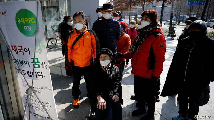 People wearing protective masks read a notice about the sale of masks at a post office amid the rise in confirmed cases of coronavirus, in Daegu, South Korea, March 5, 2020.