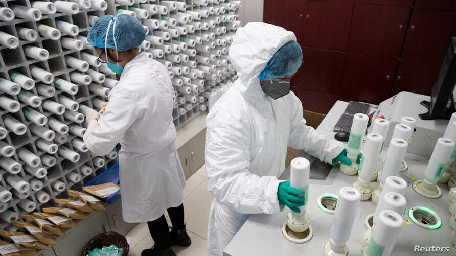 FILE - Medical personnel in protective gear prepare medicine for coronavirus-infected patients, at a pharmacy at Wuhan Tongji Hospital, in Wuhan, China, March 2, 2020. Chinese health officials say a first vaccine should soon be available.